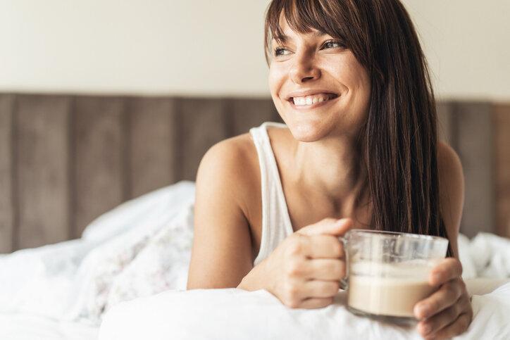 Uthvilt kvinne som sitter i en seng med kaffekopp i hånden.