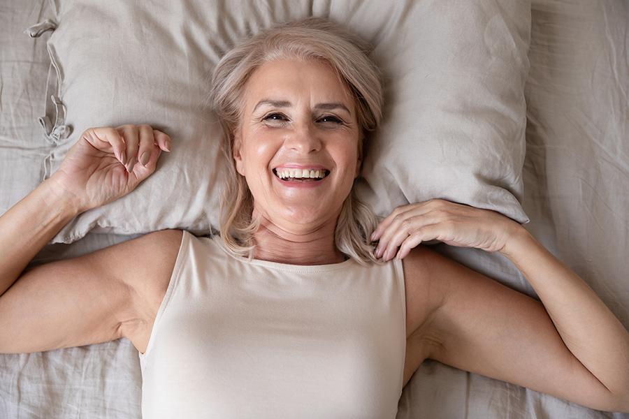 Uthvilt kvinne ligger i seng og smiler