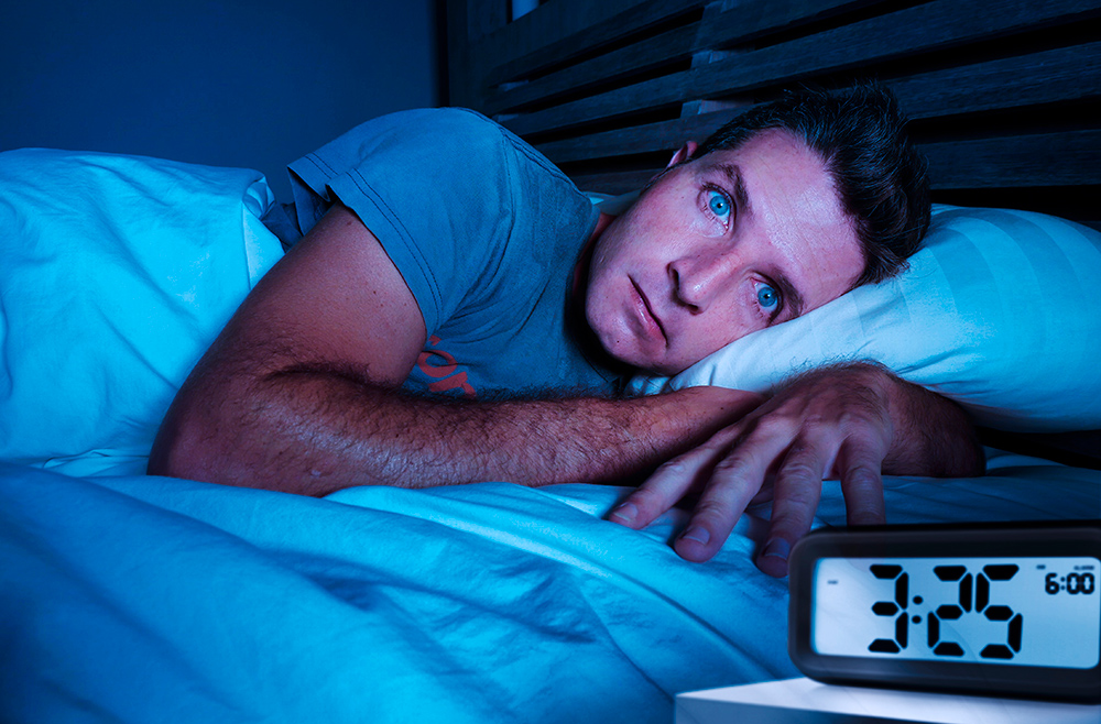 Mann i seng med søvnproblem